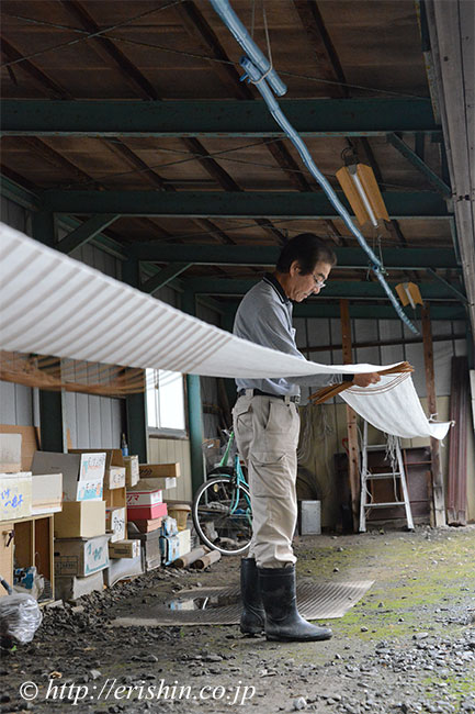 湯通しを終えた結城紬に伸子を張り、生地目を揃えながら乾かしてゆきます。